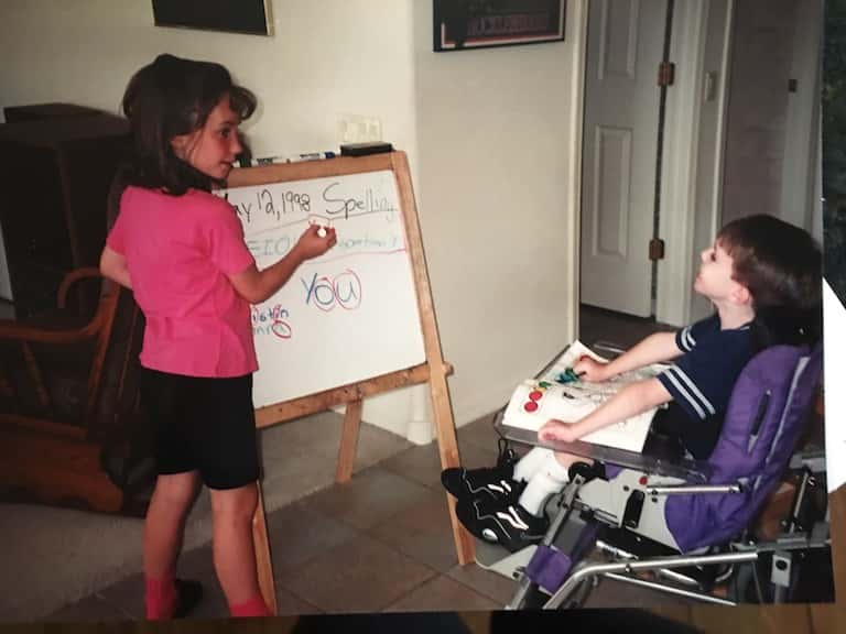 Elementary-age Kristin writing on a small white board set up in their home as younger brother Kevin, seated in a wheelchair, responds to her and works in an open spelling book in front of him.