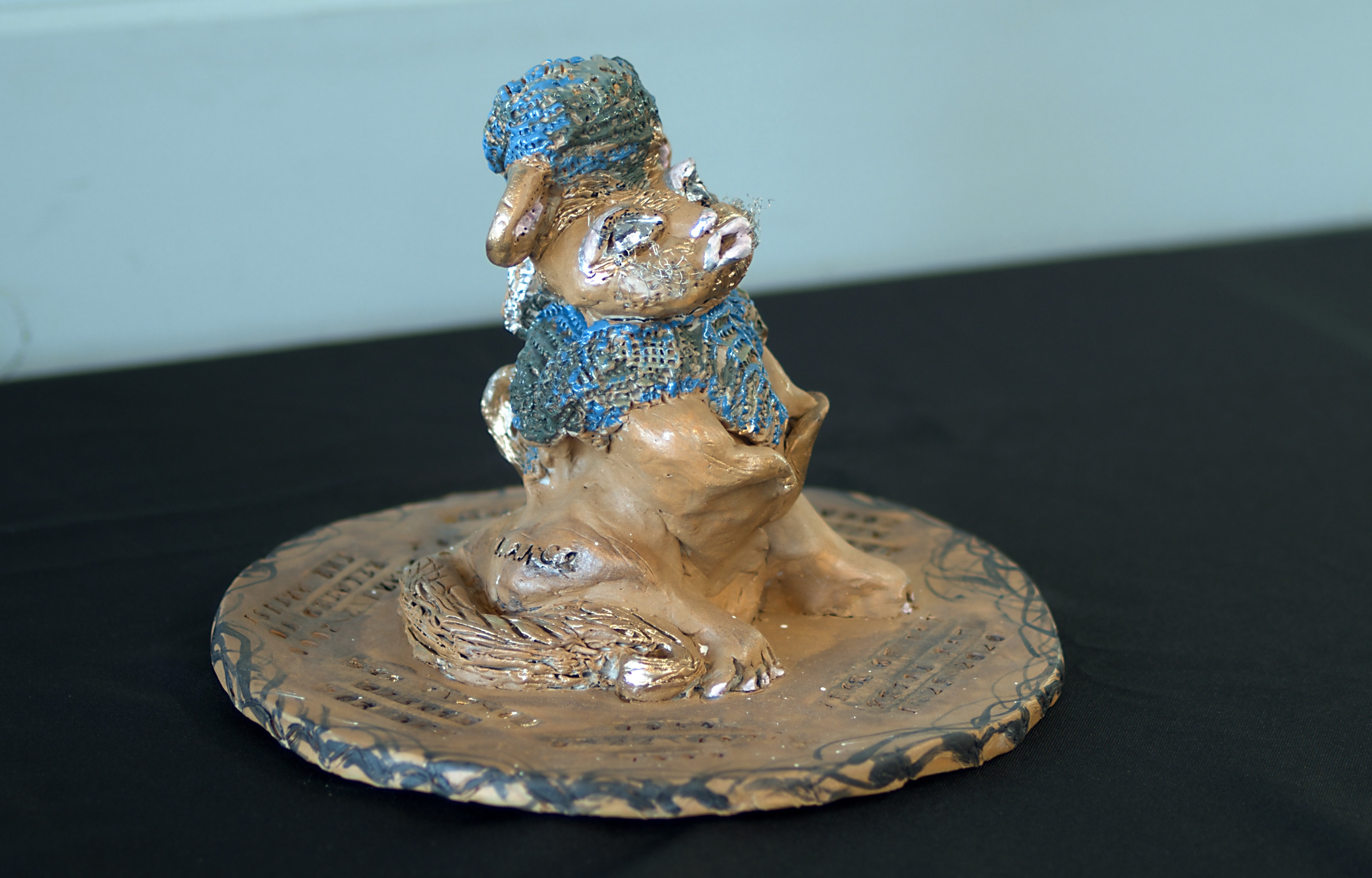 Ceramic 3d anthropomorphic rat sitting, blue headpiece and scarf, pink lips, metal whiskers. Rat sits on a circular plate with inscriptions of names and dates surrounding it.