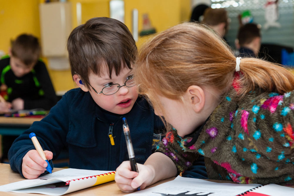 Two young children studying in a general education classroom. One of them has a disability.