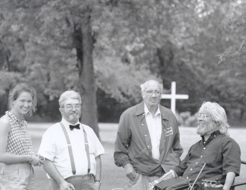 From right: Rick Cardenas, John Daggy, Cliff Poetz, and Tini at the Faribault State School cemetery, 1996. White cross in background.