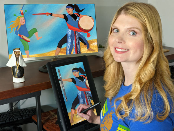 A white woman with long, straight blond hair and blue eyes looks over her shoulder toward the camera. She is wearing a bright blue shirt and holding a digital screen and pen, with a larger screen with the same image behind it. The image shows two people dancing and drumming.