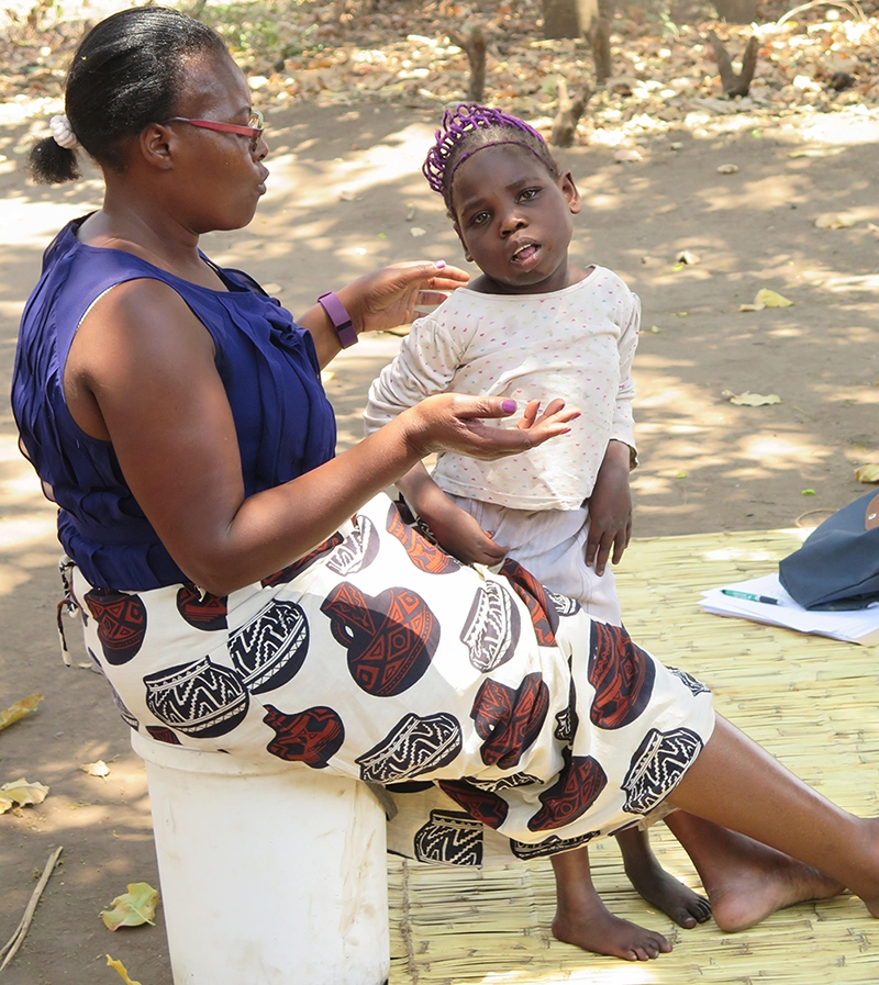ICI friend Mikala Mukongolwa teaches a child with a disability in Zambia. They are outdoors.